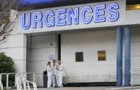 Members of the staff are seen outside the emergency services at the CHU Nord hospital in Grenoble, French Alps, where retired seven-times Formula One world champion Michael Schumacher is reported to be hospitalized after a ski accident, December 29, 2013. Schumacher suffered a head injury in a fall while skiing off-piste in the French Alps resort of Meribel on Sunday, an official said. The 44-year-old German was wearing a helmet and was conscious while being transported to a local hospital before later being transferred to to a better-equipped medical unit in Grenoble for further examinations. (REUTERS/Robert Pratta)