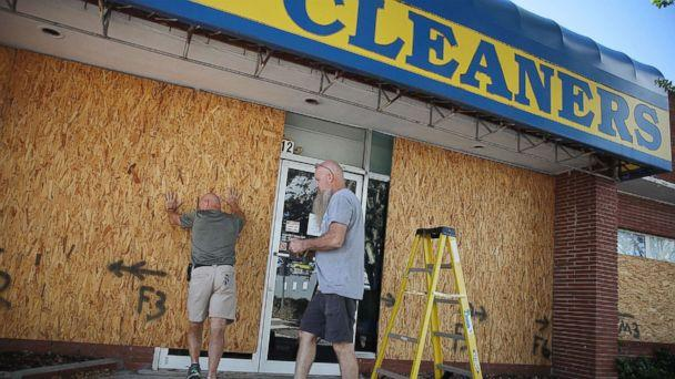 PHOTO: Michael Schwartz (L) and Jay Schwartz secure plywood over the windows of their business ahead of the arrival of Hurricane Florence, Sept. 11, 2018, in Myrtle Beach, S.C. (Joe Raedle/Getty Images)