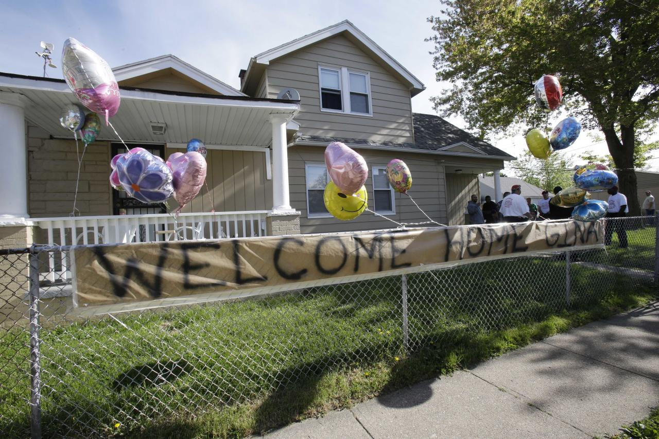 "A ""Welcome Home Gina "" sign hangs on a fence outside the home of Gina DeJesus Tuesday, May 7, 2013, in Cleveland. DeJesus, Amanda Berry and Michelle Knight, who went missing separately about a decade ago, were found in a home just south of downtown Cleveland and likely had been tied up during years of captivity, said police, who arrested three brothers. (AP Photo/Tony Dejak)"