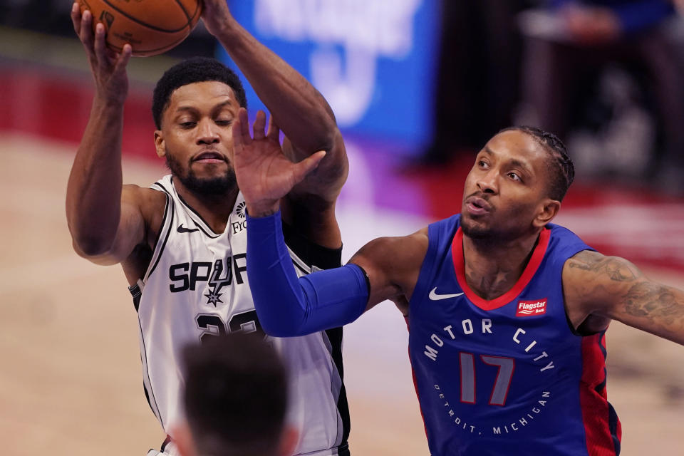Detroit Pistons guard Rodney McGruder (17) reaches in on San Antonio Spurs forward Rudy Gay during the second half of an NBA basketball game, Monday, March 15, 2021, in Detroit. (AP Photo/Carlos Osorio)