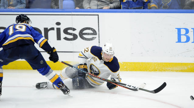 Buffalo Sabres' Johan Larsson (22), of Sweden, reaches for the puck with St. Louis Blues' Jay Bouwmeester (19) during the second period of an NHL hockey game, Thursday, Dec. 27, 2018, in St. Louis. (AP Photo/Bill Boyce)