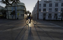 A cyclist rides past Art Deco hotels on normally bustling streets as the sun sets, Wednesday, March 25, 2020, in Miami Beach, Florida's famed South Beach. The new coronavirus causes mild or moderate symptoms for most people, but for some, especially older adults and people with existing health problems, it can cause more severe illness or death.(AP Photo/Wilfredo Lee)