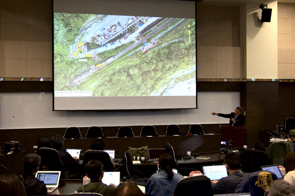 Yang Hong-chih, director of Taiwan Transportation Safety Board, at right, points to an aerial view of the site of the train derailment during a press conference held in Taipei, Taiwan on Tuesday, April 6, 2021. Investigators looking into Taiwan's deadliest railway disaster in decades combed through the crushed wreckage and debris for three days before they found the microSD chip from the dashboard camera of a construction truck that collided with a train coming out of a tunnel, officials said Tuesday. (AP Photo/Johnson Lai)