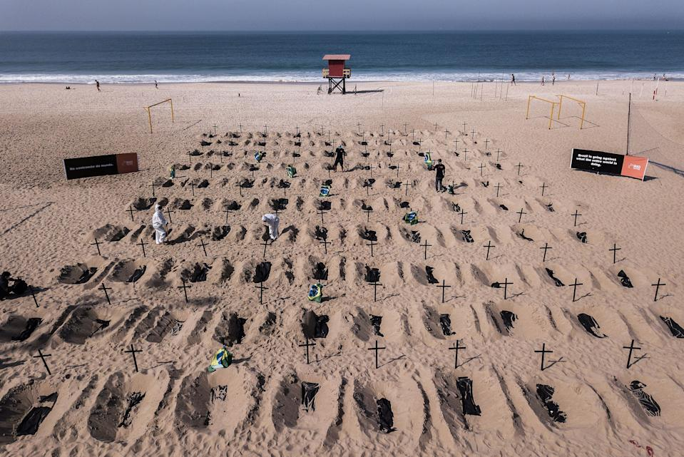 """TOPSHOT - Aerial view of activists from the Brazilian NGO Rio de Paz digging mock graves, on Copacabana beach symbolizing deaths due to the COVID-19 coronavirus and protest against Brazil's """"bad governance"""" of the pandemic, in Rio de Janeiro, Brazil, on June 11, 2020. (Photo by FLORIAN PLAUCHEUR / AFP) (Photo by FLORIAN PLAUCHEUR/AFP via Getty Images)"""