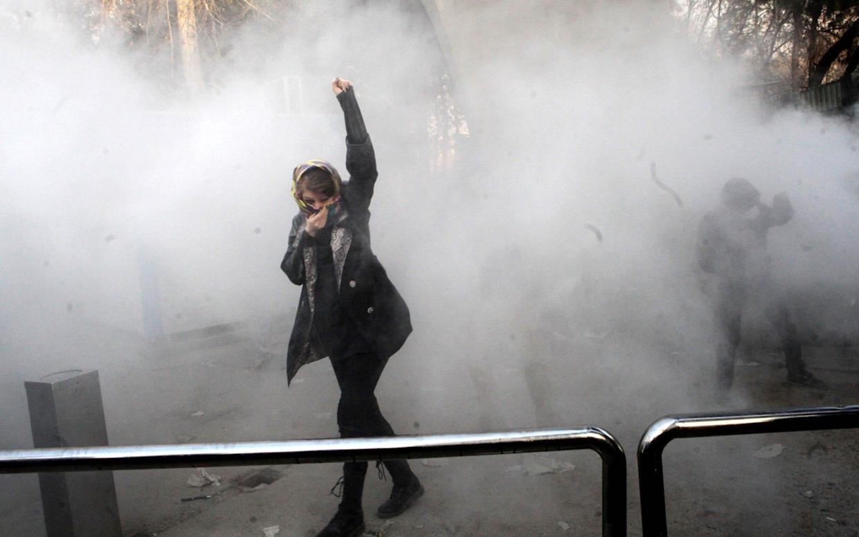An Iranian woman raises her fist amid the smoke of tear gas at the University of Tehran - AFP