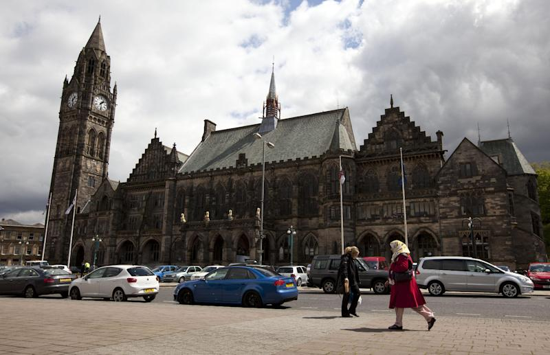 "In this Wednesday, May 16, 2012 photo, pedestrians walk past town hall in Rochdale, England. The story of the abused Rochdale girls is tragic by any measure, but it has also become explosive. Because there is no getting around its racial subtext: The girls are white, and the men who used them for sex are Asian Muslims, mostly Pakistanis raised in Britain. Louis Kushnick, founder of the race relations resource center at the University of Manchester, said it has become convenient for white residents - including those beyond the far-right movement - to blame Muslims for the sex crimes. That view overlooks all the problems that left the girls vulnerable in the first place, he says, citing a deficient school system and a government-backed child care regime riddled with neglect and abuse. And he says the prolonged economic downturn has intensified resentments, with whites and Asians competing for the same ""crap"" jobs. ""Blaming the Muslims lets us avoid addressing these questions,"" he says. ""Once we blame 'The Other,' we think we have an explanation that makes sense."" (AP Photo/Jon Super)"