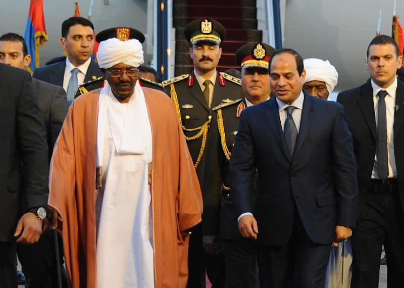 A handout picture made available by the Egyptian presidency shows Egyptian President Abdel Fattah al-Sisi (C-R) walking alongside Sudanese President Omar al-Bashir upon the latter's arrival in Red Sea resort of Sharm El-Sheikh on March 27, 2015 (AFP Photo/-)
