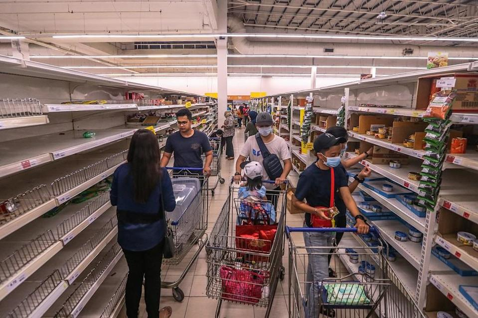People walk by near empty shelves are seen at Tesco Ampang, amid panic buying following the restriction of movement order announced by the government, in Kuala Lumpur March 17, 2020. — Picture by Firdaus Latif