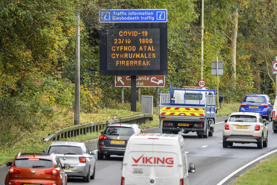 "A matrix sign on the A48(M) heading towards Cardiff informing motorists to Wales entering a ""firebreak"" lockdown, Friday, Oct. 23, 2020. A police force in England says it will try to stop people from leaving Wales, which has started a 17-day lockdown to slow the spread of COVID-19. The Gloucestershire Constabulary says it will patrol routes from Wales and pull over drivers they believe are making long journeys. Travelers without a good excuse will be asked to turn around. (Ben Birchall/PA via AP)"