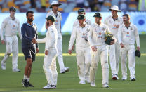 India's Cheteshwar Pujara, second left, is congratulated by Australia's Matthew Wade after defeating Australia by three wickets on the final day of the fourth cricket test at the Gabba, Brisbane, Australia, Tuesday, Jan. 19, 2021.India won the four test series 2-1. (AP Photo/Tertius Pickard)
