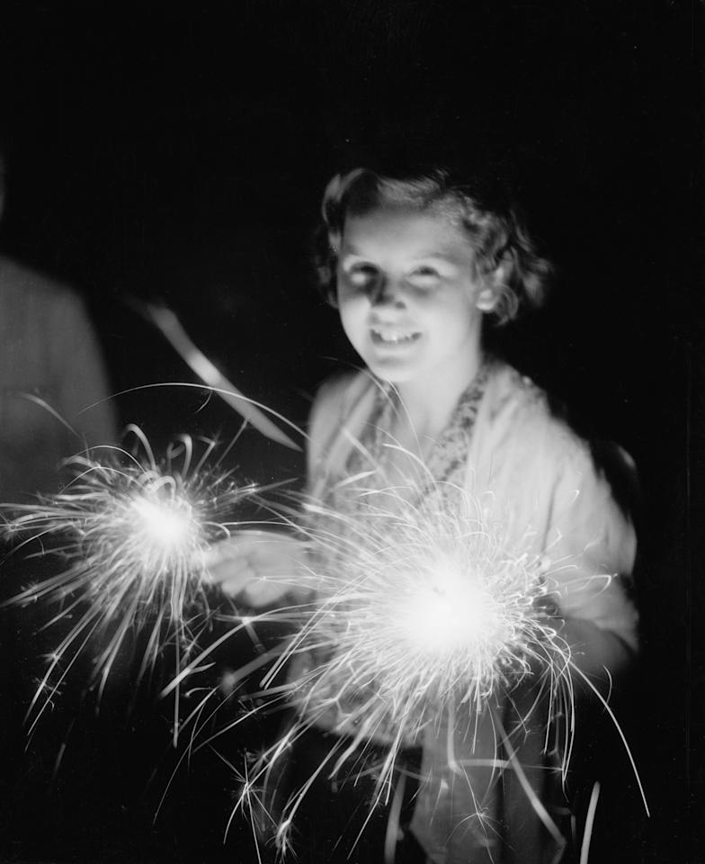 <p>Girl with sparklers, 1930. (Photo: Bettmann Archive/Getty Images) </p>