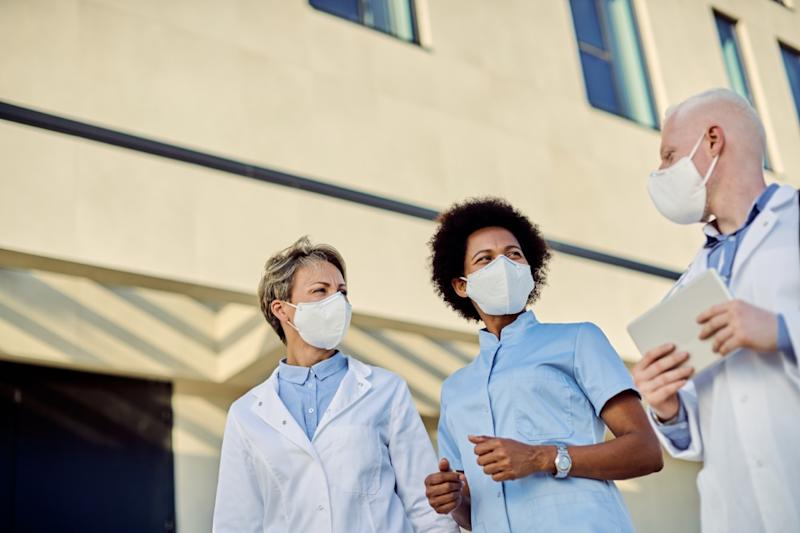 group of doctors talking outdoors while wearing face masks