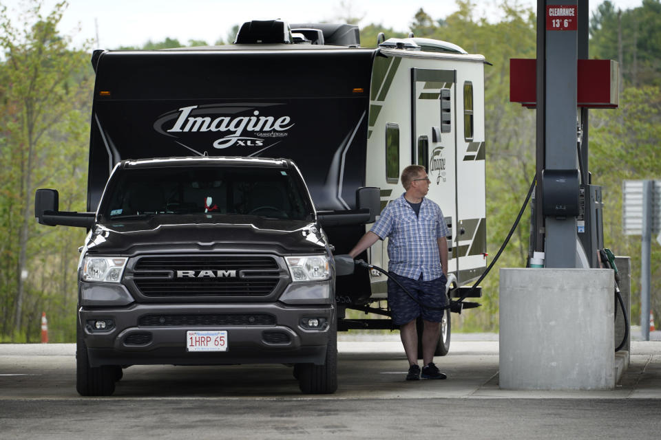 A motorist from Massachusetts fills his truck with gas at a rest area on the Maine Turnpike, Friday, May 28, 2021, in Kennebunk, Maine. The state expects a large increase in the number of out-of-state visitors over last year when the COVID-19 pandemic forced a lot of businesses to close. (AP Photo/Robert F. Bukaty)
