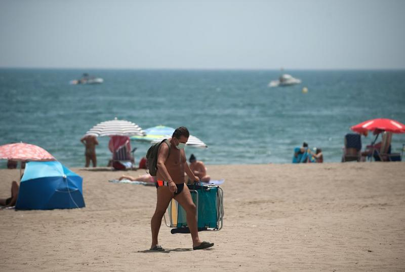 A man wearing a face mask carrying chairs at Rincon Sol beach of Torremolinos in Malaga during a hot summer day.