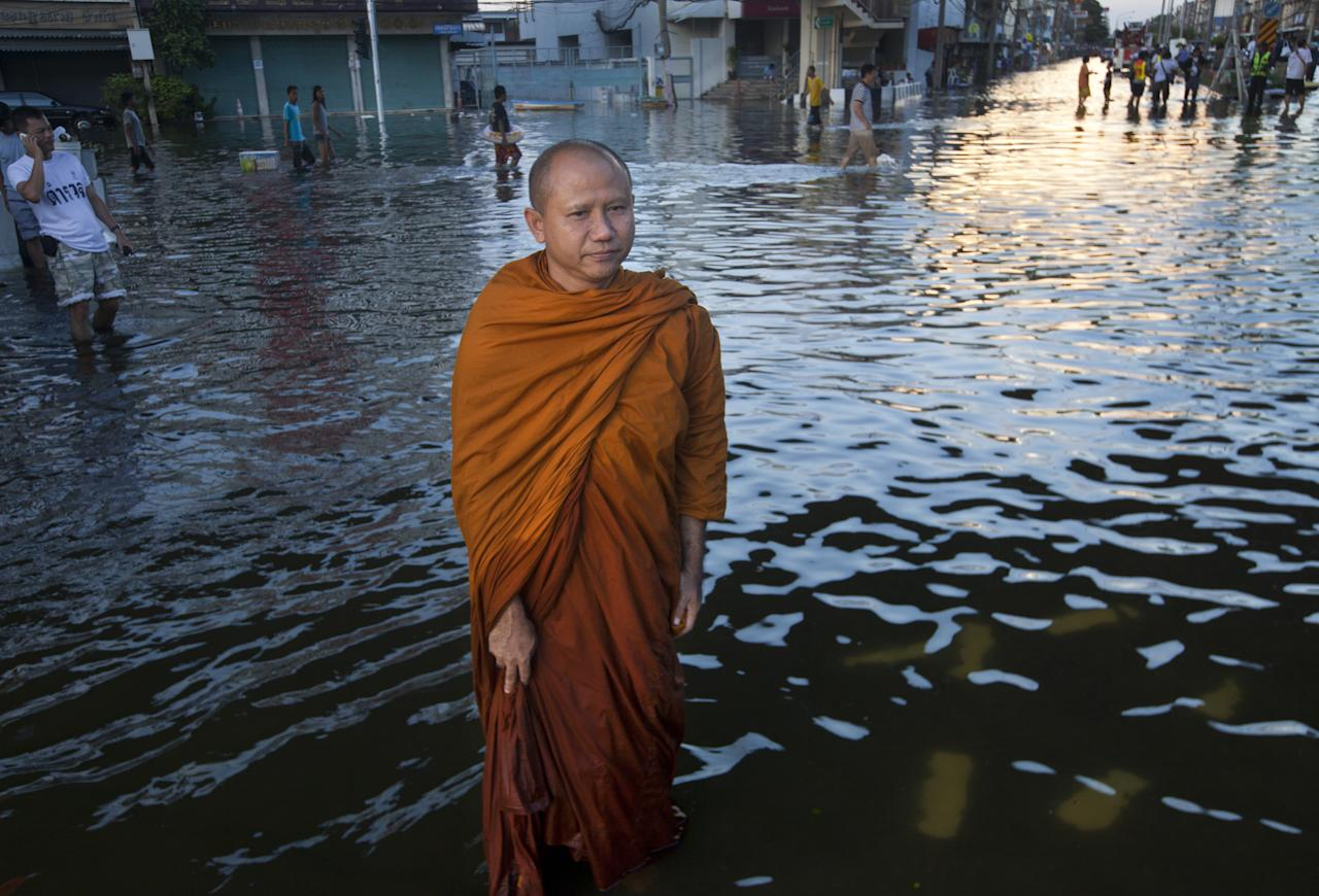 BANGKOK, THAILAND - OCTOBER 29: A Thai monk stands in a flooded neighborhood near the Chayo Praya river as rising waters threaten parts of the capitol city on October 29, 2011 in Bangkok, Thailand. Thailand is experiencing the worst flooding in over 50 years which has affected more than nine million people and caused the closure of hundreds of factories in the central Thai province of Ayutthaya and Nonthaburi. Over 370 people have died in flood-related incidents since late July according to the Department of Disaster Prevention and Mitigation.  (Photo by Paula Bronstein /Getty Images)
