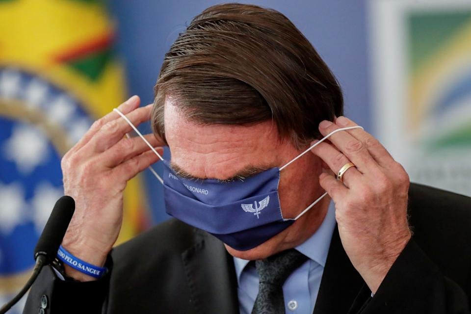 Brazil's President Jair Bolsonaro tries to put his mask on during a ceremony to announce investments for the Aguas Brasileiras Program (program brazilian water) at the Planalto Palace in Brasilia, Brazil, March 22, 2021. REUTERS/Ueslei Marcelino     TPX IMAGES OF THE DAY