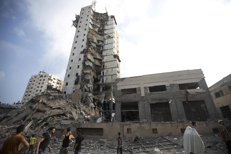 Palestinians look up at the remains of an Italian apartment block that was destroyed by an Israeli air strike overnight in Gaza City on August 26, 2014