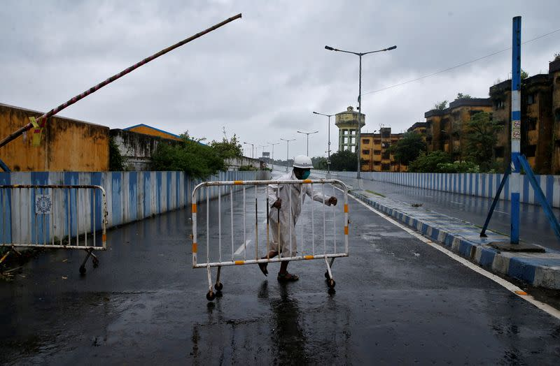 A police officer moves a barricade to block a road before Cyclone Amphan makes its landfall, in Kolkata