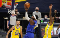 Denver Nuggets forward Paul Millsap, center, drives to the rim as Golden State Warriors guard Stephen Curry, left, and forward Andrew Wiggins defend in the first half of an NBA basketball game Thursday, Jan. 14, 2021, in Denver. (AP Photo/David Zalubowski)
