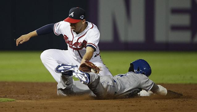 Los Angeles Dodgers' Dee Gordon, right, tries to steal second base as Atlanta Braves shortstop Andrelton Simmons, left, makes the tag in the ninth inning of Game 2 of the National League division series on Friday, Oct. 4, 2013, in Atlanta. The Braves won 4-3. (AP Photo/John Bazemore)