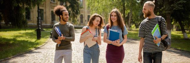 Diverse group of college students walking on campus