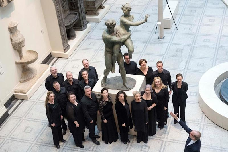 The Royal Opera chorus perform around The Rape of Proserpina sculpture at the V&A.