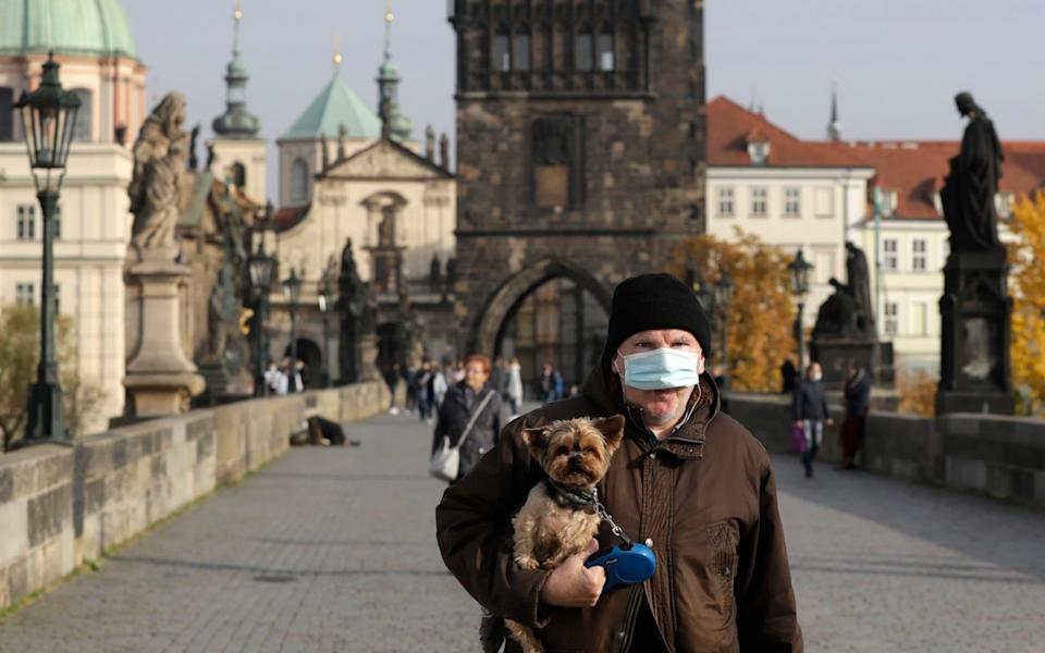 A man wearing a face mask carries his dog across the medieval Charles Bridge. Infections are spiraling in the Czech Republic, where the government is introducing new restrictions - AP Photo/Petr David Josek