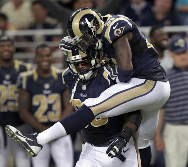 St. Louis Rams defensive end Michael Sam, left, is congratulated by teammate Maurice Alexander after Sam sacked Green Bay Packers quarterback Matt Flynn for a 10-yard loss during the fourth quarter of an NFL preseason football game Saturday, Aug. 16, 2014, in St. Louis. (AP Photo/Tom Gannam)