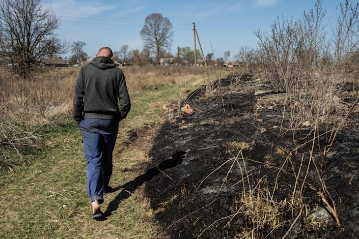 Image: Andriy Budych, 27, who didn't want his face to be shown, walks near the place where he recently set garbage and grass on fire, which according to police then spread to the Chornobyl Exlusion Zone, in the village of Rahivka, Kyiv region, Ukraine (Oksana Parafeniuk / for NBC News)