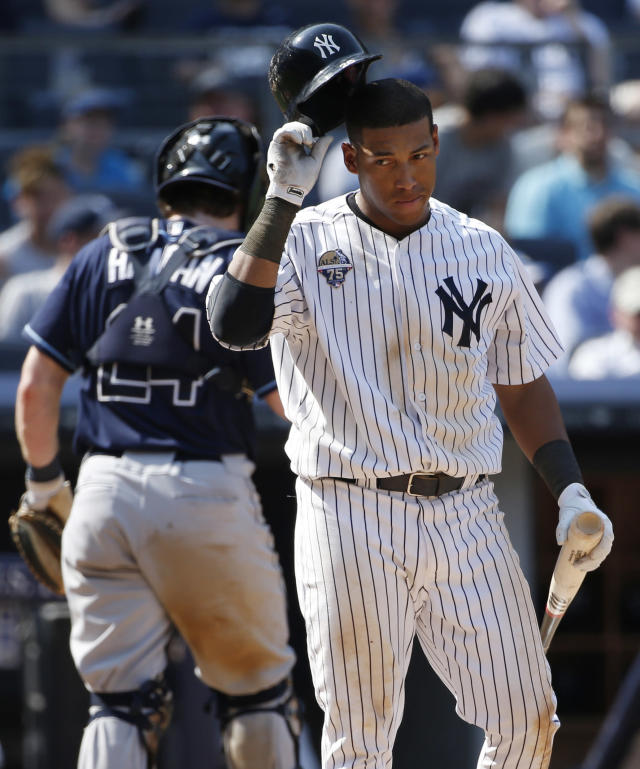 FILE - In this July 2, 2014, file photo, New York Yankees Yangervis Solarte removes his batting helmet after striking out with a runner on second in the eight inning of a baseball game against the Tampa Bay Rays at Yankee Stadium in New York. Trying to add offense at third base, the Yankees have acquired Chase Headley from the San Diego Padres on Tuesday, July 22, 2014, for infielder Yangervis Solarte and right-hander Rafael De Paula. (AP Photo/Kathy Willens, File)