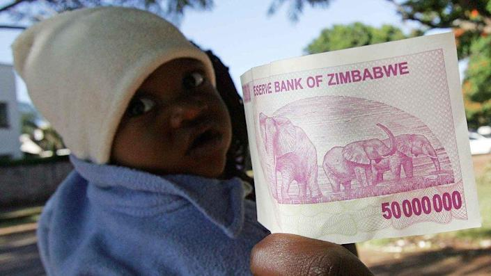 Zimbabwe's new fifty million dollar note, issued by the Reserve Bank on April 4, 2008, is pictured in Harare next to a toddler.