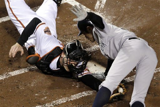 New York Yankees' Ichiro Suzuki, right, of Japan, leaps past Baltimore Orioles catcher Matt Wieters to score a run on a double by Robinson Cano in the first inning of Game 2 of the American League division baseball series on Monday, Oct. 8, 2012, in Baltimore. (AP Photo/Patrick Semansky)