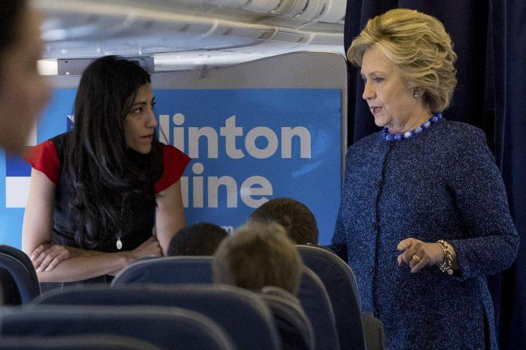 Hillary Clinton speaks with senior aide Huma Abedin aboard her campaign plane. (Photo: Andrew Harnik/AP)