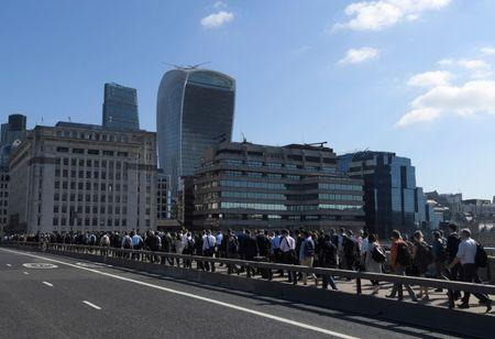 Workers cross London Bridge with skyscrapers in the City of London seen behind during the morning rush hour in London, Britain
