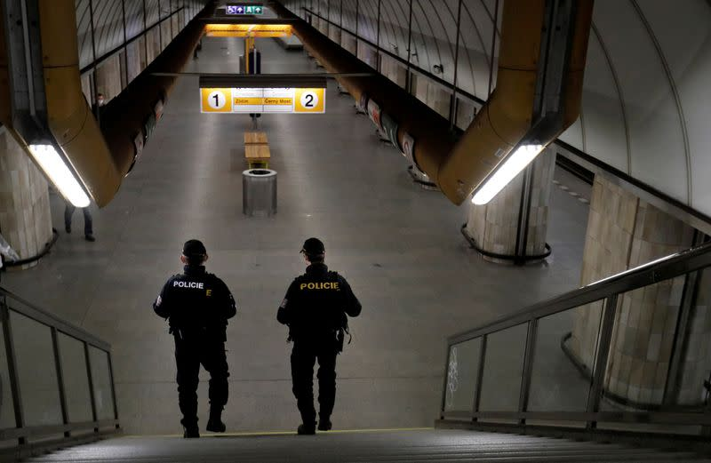 FILE PHOTO: Police officers patrol at a nearly empty subway station in Prague