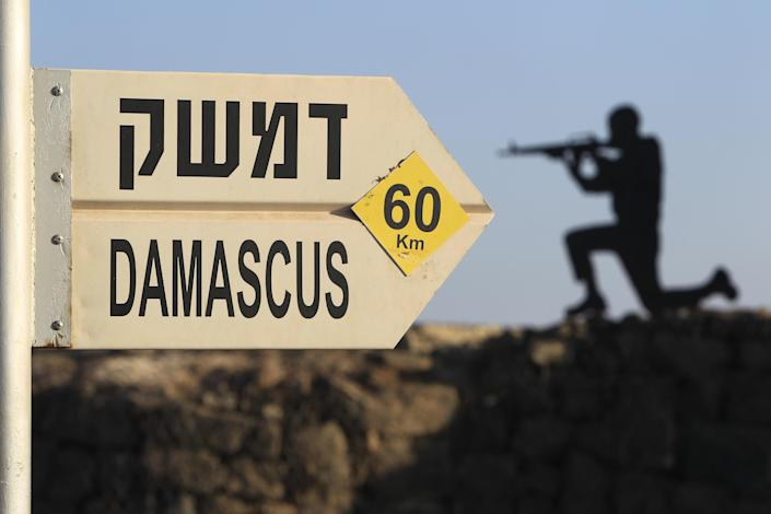 In this photo taken Tuesday, July 24, 2012 photograph, a sign showing the distances to Damascus and a cut out of a soldier are seen at an army post from the 1967 war at Mt. Bental in the Golan Heights, overlooking Syria. (AP Photo/Tsafrir Abayov)