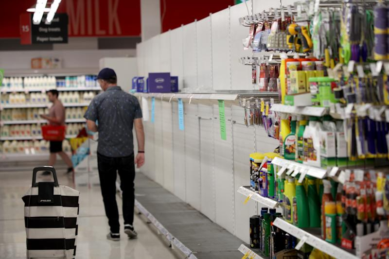 Two Coles shoppers are walking inside an Adelaide store where the toilet paper aisle is empty.