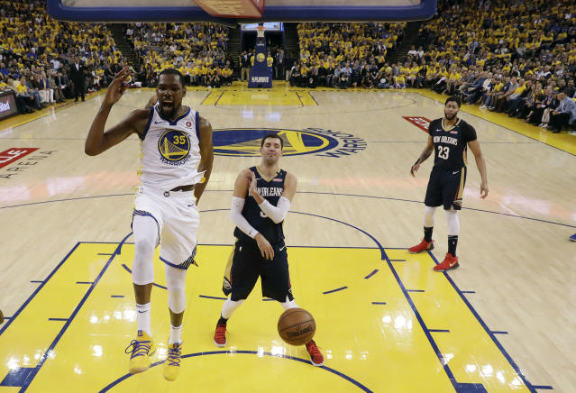 Golden State Warriors' Kevin Durant (35) reacts after dunking past New Orleans Pelicans' Nikola Mirotic, center, during the first half in Game 5 of an NBA basketball second-round playoff series Tuesday, May 8, 2018, in Oakland, Calif. (AP Photo/Marcio Jose Sanchez)
