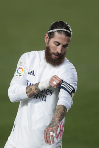 Real Madrid's Sergio Ramos adjusts his captain's band during the Spanish La Liga soccer match between Real Madrid and Granada at the Alfredo Di Stefano stadium in Madrid, Spain, Wednesday, Dec. 23, 2020. (AP Photo/Bernat Armangue)