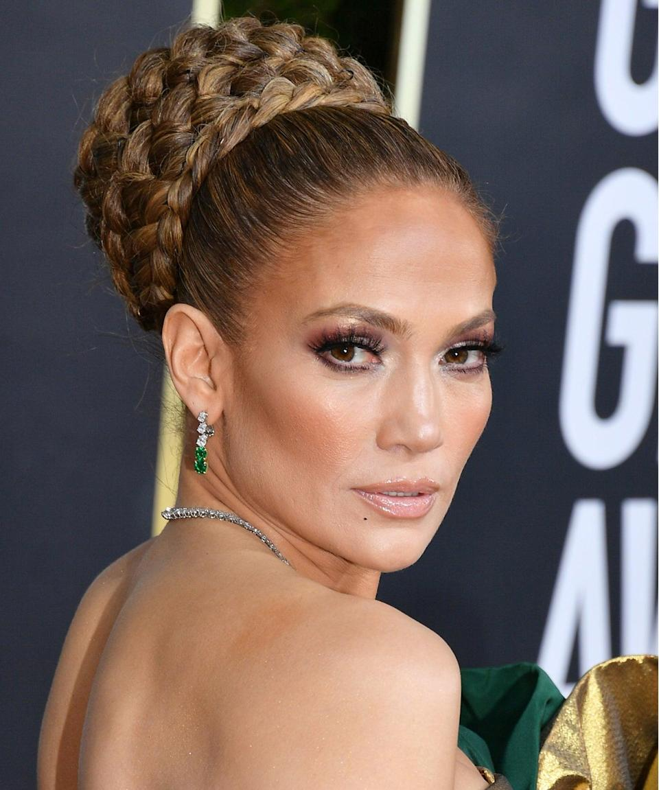 """<h3>2020</h3><br>Lopez arrived at the 77th Golden Globes with a beauty look worthy of its own accolade. The nominee wore a regal structured bun wrapped in French braids, which complemented her smoky eyes and chiseled cheeks. <span class=""""copyright"""">Photo: George Pimentel/WireImage.</span>"""