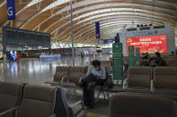 Passengers take rest near a blank flights information board at Pudong International Airport in Shanghai, China, Sunday, July 25, 2021. Airline flights were canceled in eastern China and cargo ships were ordered out of the area Saturday as Typhoon In-fa churned toward the mainland after dumping rain on Taiwan. (AP Photo/Andy Wong)