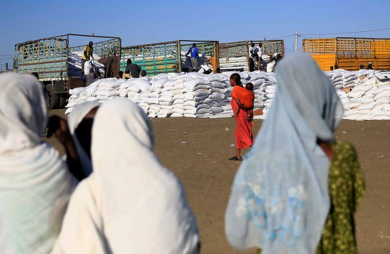 Women watch as workers off-load sacks of food from trucks to deliver it to Ethiopian refugees fleeing from the ongoing fighting in Tigray region, at the Fashaga camp, on the Sudan-Ethiopia border, in Kassala state