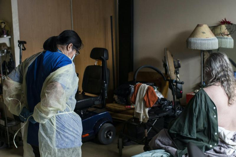 A personal support worker puts on a plastic robe while her client sits on the bed waiting for her help. Wheelchairs sit next to the bed.