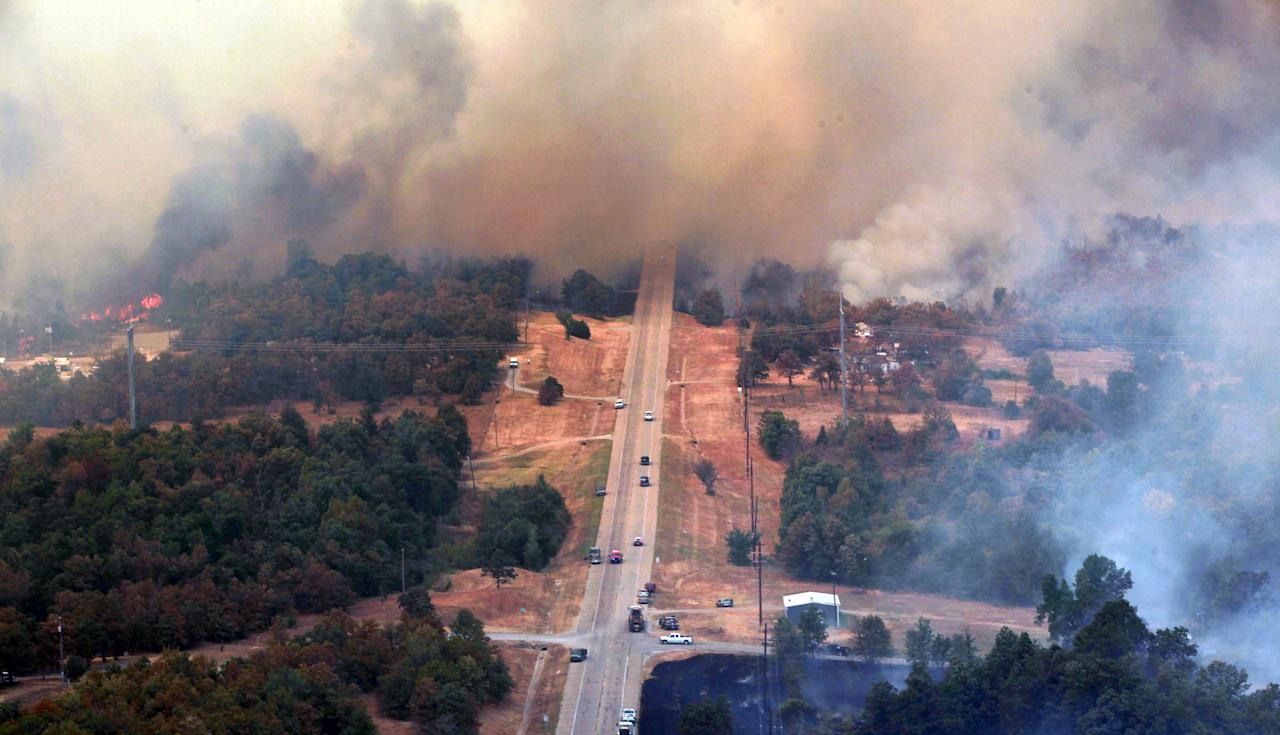 Highway 48 is covered in smoke as flames continue, Saturday, Aug 4, 2012, east of Drumright, Okla. Emergency management officials have ordered evacuations of homes in several areas as wildfires burn across the state. The Oklahoma Department of Emergency Services says no injuries have been reported. (AP Photo/Tulsa World, Tom Gilbert)