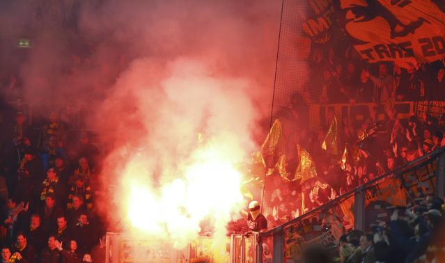 Supporters burn Bengalo flare before the German Cup (DFB Pokal) soccer match between Dynamo Dresden and Borussia Dortmund in Dresden March 3, 2015. REUTERS/Hannibal Hanschke (GERMANY - Tags: SOCCER SPORT) DFB RULES PROHIBIT USE IN MMS SERVICES VIA HANDHELD DEVICES UNTIL TWO HOURS AFTER A MATCH AND ANY USAGE ON INTERNET OR ONLINE MEDIA SIMULATING VIDEO FOOTAGE DURING THE MATCH.