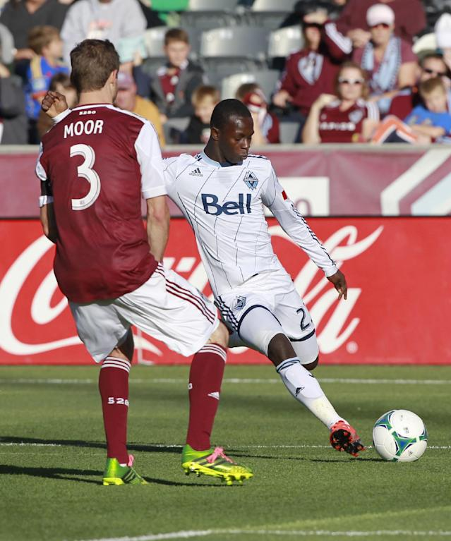 Vancouver Whitecaps forward Kekuta Manneh, back, takes a shot on goal as Colorado Rapids defenseman Drew Moor comes in to cover in the first half of a MLS soccer game in Commerce City, Colo., on Saturday, Oct. 19, 2013. (AP Photo/David Zalubowski)