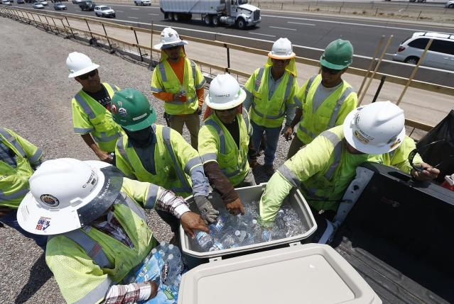 <p>Crew members building the Loop 202 South Mountain Freeway take a break as they try to keep hydrated and stay cool as temperatures climb to near-record highs, June 20, 2017, in Phoenix. (Ross D. Franklin/AP) </p>