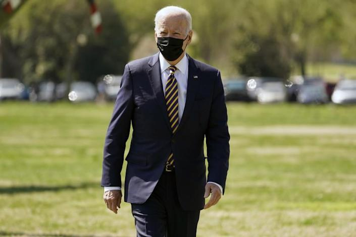 After arriving at the National Mall ellipse, President Joe Biden walks to talk to members of the media