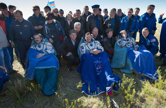 Expedition 35 Commander Chris Hadfield of the Canadian Space Agency (CSA), left, Russian Flight Engineer Roman Romanenko of the Russian Federal Space Agency (Roscosmos), center, and NASA Flight Engineer Tom Marshburn sit in chairs outside the S
