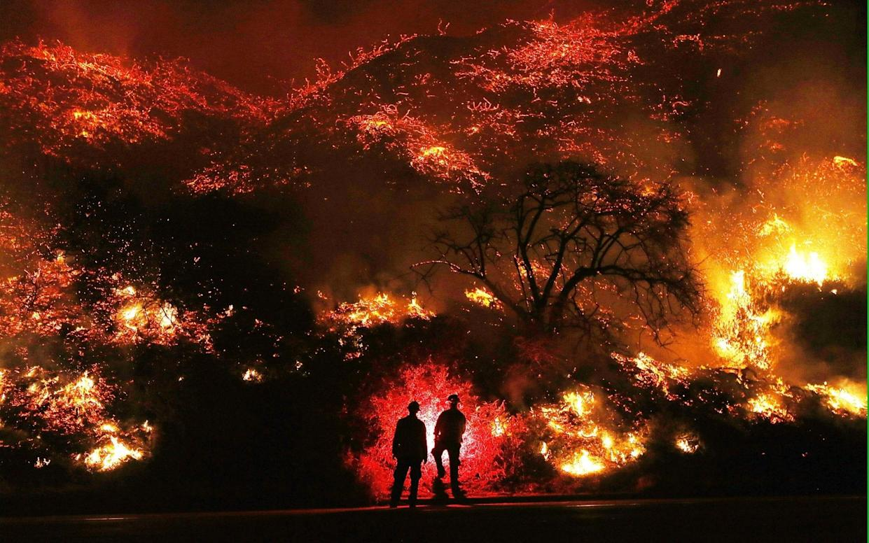 Firefighters monitor a section of the Thomas Fire along the 101 freeway north of Ventura, California - Getty Images North America